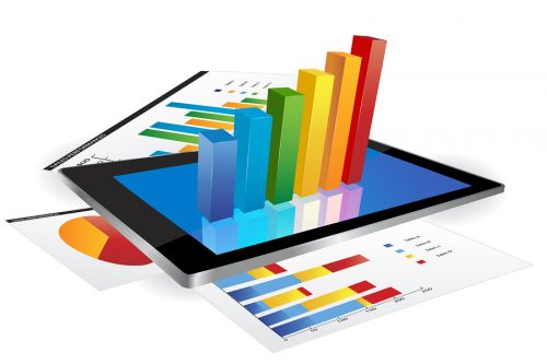Tablet screen with 3d graph and a paper with statistic charts